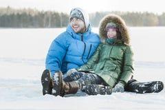 获得年轻的夫妇乐趣户外坐多雪的地面覆盖物在冬天飞雪期间 免版税库存图片
