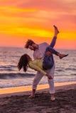 获得年轻的夫妇在含沙海岸的乐趣 图库摄影