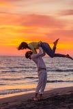 获得年轻的夫妇在含沙海岸的乐趣 免版税图库摄影