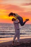 获得年轻的夫妇在含沙海岸的乐趣 库存图片