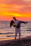 获得年轻的夫妇在含沙海岸的乐趣 库存照片