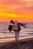 获得年轻的夫妇在含沙海岸的乐趣 免版税库存图片