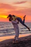 获得年轻的夫妇在含沙海岸的乐趣 免版税库存照片