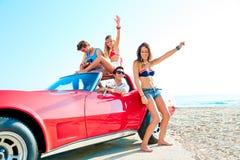 获得年轻的小组在弹吉他的海滩的乐趣 库存图片
