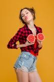 获得滑稽的嬉戏的妇女与两个一半的乐趣葡萄柚 库存照片