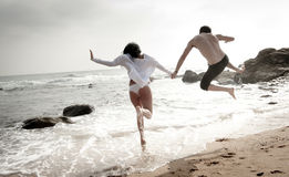 获得年轻美好的夫妇跳跃沿海滩的乐趣 免版税库存照片