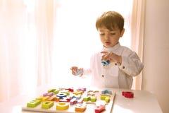 获得活跃孩子的男孩与木信件的乐趣 图库摄影