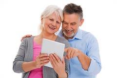 获得年长的夫妇与技术的乐趣 免版税库存图片