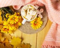 菊花咖啡与甜点的,花束和在秋叶背景的温暖的围巾  免版税库存图片