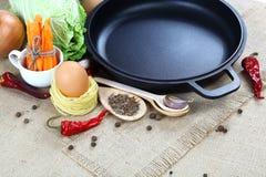 菜、香料和厨房器物在麻袋布 免版税库存照片