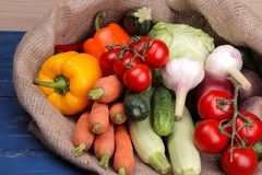 菜包括大蒜黄瓜圆白菜葱以子弹密击甜菜根红萝卜夏南瓜和蕃茄在一个袋子在一张蓝色木桌上 免版税库存照片