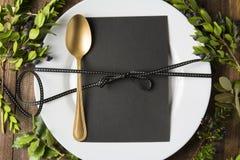 菜单与空的卡片的餐位餐具和在木背景的金黄匙子,围拢由绿色分支 免版税库存图片