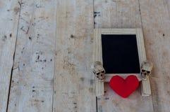 菜单板在黑和红色心脏和一块人的头骨在w放置 库存图片