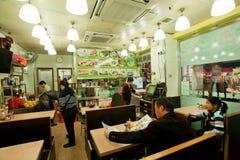 读菜单用异乎寻常的食物的人们在小中国餐馆 免版税图库摄影