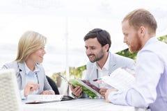 读菜单的愉快的买卖人在边路咖啡馆 免版税库存图片