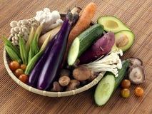菜和产物篮子在竹桌上 免版税库存照片