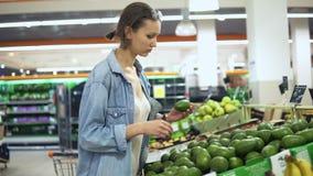 菜和果子部门在杂货店 偶然选择的绿色鲕梨的俏丽的女孩 手扶的英尺长度 影视素材