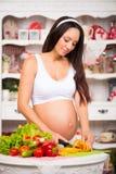 菜和饮食在怀孕期间 美丽的孕妇在准备膳食的厨房里 免版税图库摄影