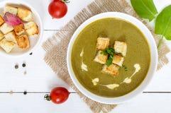 菜奶油色汤用菠菜和土豆在一个白色碗用大蒜油煎方型小面包片在黑暗的木背景 免版税库存图片