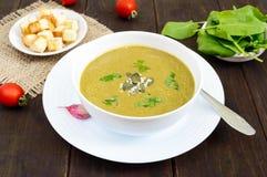 菜奶油色汤用菠菜和土豆在一个白色碗用大蒜油煎方型小面包片在黑暗的木背景 免版税库存照片