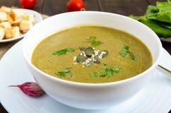 菜奶油色汤用菠菜和土豆在一个白色碗用大蒜油煎方型小面包片 库存照片