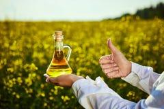 菜子油瓶在手中一名农艺师或生物学家背景强奸领域的 库存照片