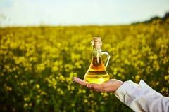 菜子油瓶在手中一名农艺师或生物学家背景强奸领域的 免版税库存图片