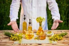 菜子油瓶在手中一名农艺师或生物学家背景强奸领域的 库存图片