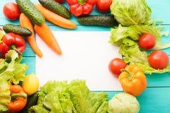 菜框架与白色拷贝空间的在蓝色木桌上 顶视图和嘲笑 复制空间 模板和空白的食谱纸 免版税库存图片