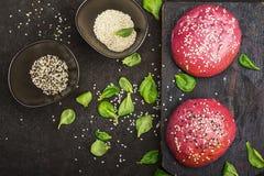 菜汉堡的桃红色小圆面包根据与芝麻籽的甜菜在黑暗的背景 顶视图 库存照片