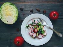 菜沙拉和一半白人圆白菜和两个红色蕃茄在桌上说谎 免版税库存照片