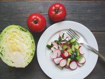 菜沙拉和一半白人圆白菜和两个红色蕃茄在桌上说谎 免版税图库摄影