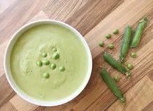 菜浓豌豆汤 豆类汤和新鲜的豌豆在木桌上 顶视图 库存照片