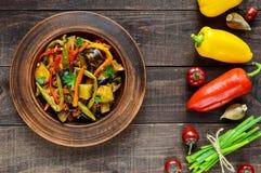 菜炖煮的食物沙拉:甜椒,茄子,芦笋豆,大蒜,红萝卜,韭葱 明亮的辣芳香盘 图库摄影