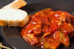 菜炖煮的食物用在黑色的盘子和桌布的面包 库存图片
