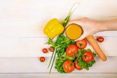 菜特写镜头品种在浅褐色的木背景的 可口蕃茄和胡椒 有一杯的手汁液 库存图片