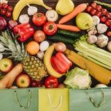 菜用果子和在木桌上的购物袋顶视图  库存图片