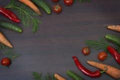 菜的概念在木棕色背景的 绿色黄瓜和蕃茄在一张木桌上 红萝卜和辣椒粉与绿色 免版税库存图片