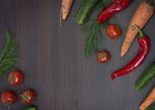 菜的概念在木棕色背景的 绿色黄瓜和蕃茄在一张木桌上 红萝卜和辣椒粉与绿色 库存图片