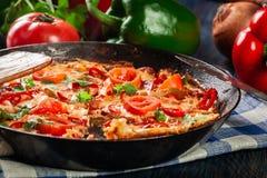 菜肉馅煎蛋饼由鸡蛋、香肠加调料的口利左香肠、红辣椒、青椒、蕃茄、乳酪和辣椒制成在平底锅在木桌 免版税库存照片