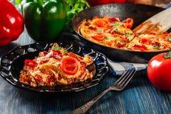 菜肉馅煎蛋饼的部分用鸡蛋、香肠加调料的口利左香肠、红辣椒、青椒、蕃茄、乳酪和辣椒在一块板材在木桌上 库存图片