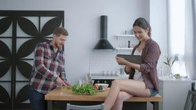 菜营养饮食,有胡子的人准备从新鲜蔬菜的可口健康沙拉,并且绿色和妇女坐 股票录像
