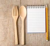 菜谱、铅笔和厨具在木背景 免版税库存图片