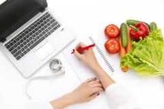 菜饮食营养或药剂概念 写饮食的医生手计划,成熟菜构成,膝上型计算机和测量 免版税图库摄影
