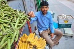 菜贸易商微笑坐在他的商品,来自南方的风暴旁边 免版税图库摄影