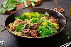菜-硬花甘蓝、蘑菇、菠菜和奎奴亚藜健康素食主义者沙拉在碗 库存图片