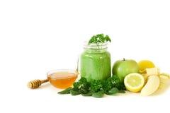 从菠菜、荷兰芹、苹果、香蕉、柠檬和蜂蜜的绿色菜圆滑的人 免版税库存照片