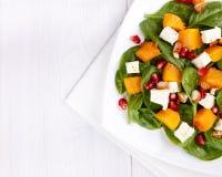 菠菜叶子、被烘烤的南瓜和希腊白软干酪沙拉与almo 免版税库存图片