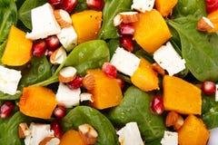 菠菜叶子、被烘烤的南瓜和希腊白软干酪沙拉用杏仁和石榴种子作为背景 图库摄影