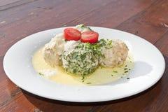 菠菜和乳酪Knodels服务用熔化黄油加上巴马干酪 免版税库存图片